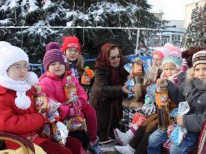 Galina BACALÂM (în centru), de rând cu copiii veniți la Pomul ce Crăciun din centrul orașului Drochia, împărtășește bucuria sărbătorilor