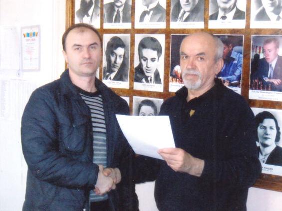 Председатель шахматно-шашечного клуба Валерий Пашигрев вручает грамоту чемпиону города Сергею Бежан