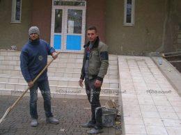 Строители завершают работу по укладке плитки во дворе