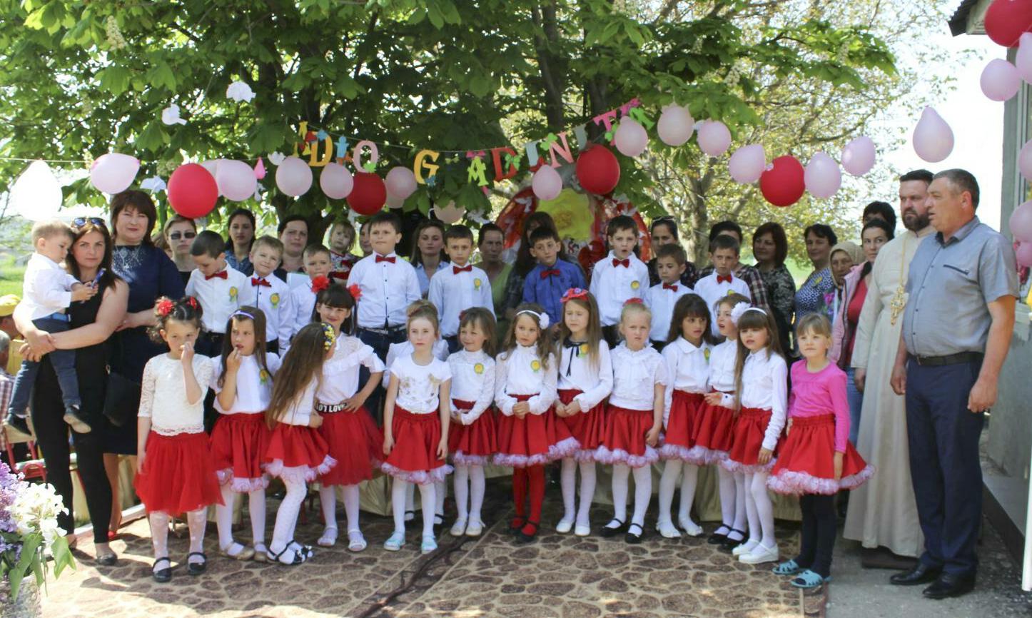 """Copiii de la grădinița """"Scufița Roșie"""", din satul Drochia, împreună cu educatorii, părinții, parohul bisericii și primarul satului"""