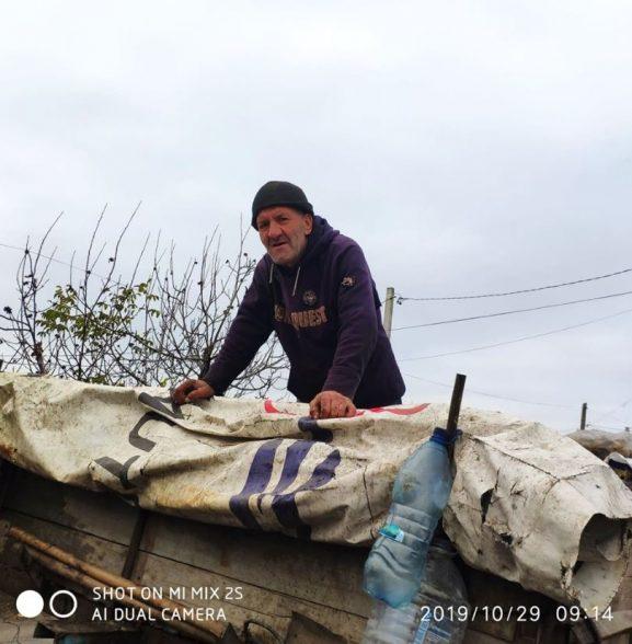 Ion Sârbu așează cu grijă gunoiul în remorcă pentru a încăpea cât mai mult